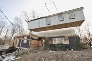 Crane adding second story to house.