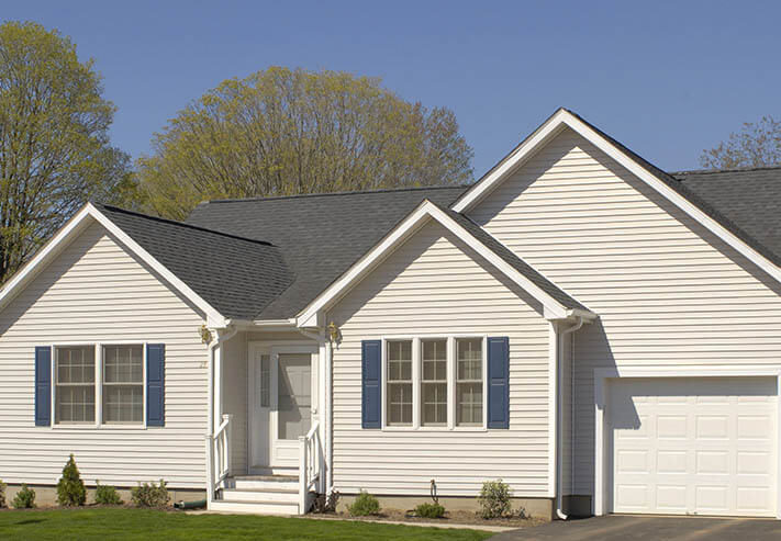 cream colored ranch style home with blue shutters